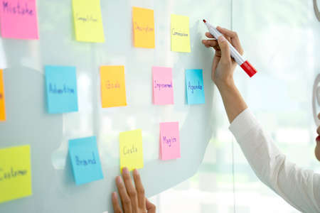 Businesswoman uses a pen in her hand to write a note on a notepad on white board to remind and brainstorm business ideas.