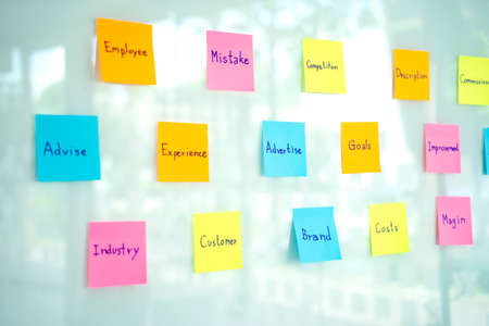 Lots of sticky note paper get stuck on the glass for group of staff to find the ideal in  business planning.