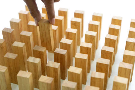 Young man holds the wood block in his hand to put it into the row to protect the domino effect business concept 版權商用圖片