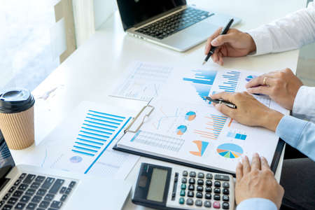 Businessman pointing at  graphs paper of business in a graph analysis in office Marketing chart for marketing planning to generate sales 版權商用圖片