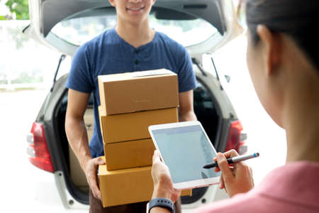The courier stood holding the box with a smile delivering the product box to the customer who was signing on the tablet concept e-comercial