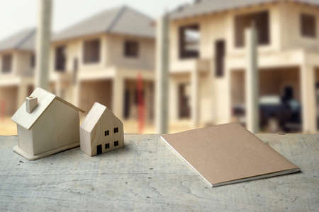 house model on The white table with notebook  and a village project in the background in real estate project. 版權商用圖片