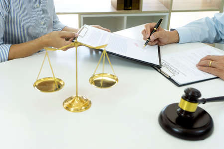 In a law firm, officers are bringing contract documents attorney to  sign on a table with gavel and balance. 版權商用圖片