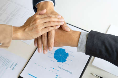 Businessmen stack their hands to show cooperation after a business deal meeting team partnership or as a congratulatory sign. 版權商用圖片
