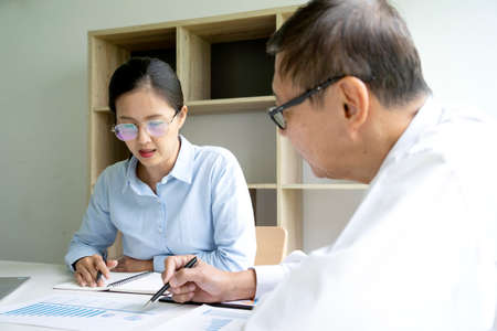 Businesswoman intern asking questions about online project to serious confident mentor they pointing at the paper on the table