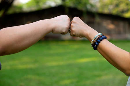 Close up image of two hand fist bump at the outdoor area green background to show their feeling friendship and happy