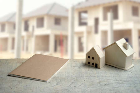 The white table had a house model and a notebook  and a village project in the background in real estate project.