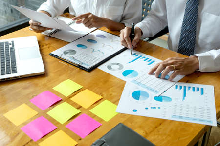 Business men and women are having a business plan consultation meeting by bringing information and graphs to study by putting notepads on the table to prepare to write idea