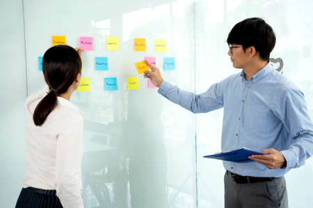 Businessmen and woman are standing He giving advice and brainstorming for Find an ideal and Write to notepad and stick it on the board.