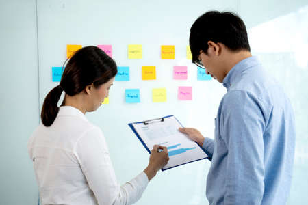 businessman explaining about the business marketing operation to an assistant or staff team he points to the paper graph on the clip board and note post on the wall in the background. 版權商用圖片