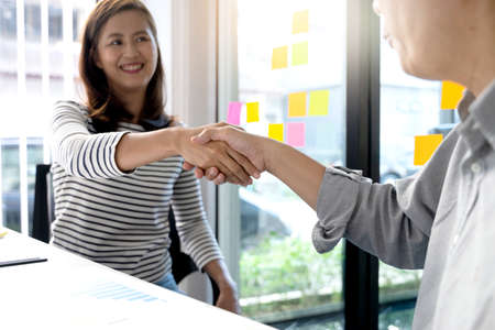 Two business people are shaking hands to congratulate them on a successful business deal.