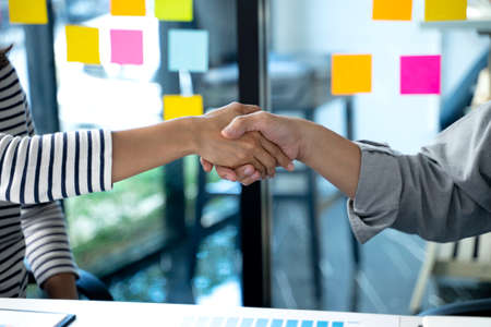 Business men and women are caught on after a successful business deal  handshake