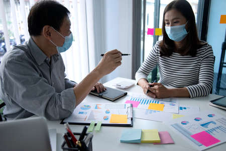 business man woman consulting in meeting wearing mask to prevent 版權商用圖片