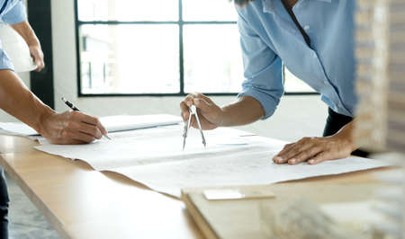 architect or engineer working on table use drawing tool on the  paper plan  for business architectural project near the building model houses.