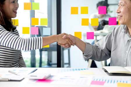 Two smile business people are shaking hands to congratulate them on a successful business deal. 版權商用圖片