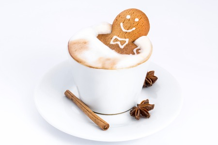 Delicious cookies in the shape of a man taking a bath in a cappuccino in a white cup