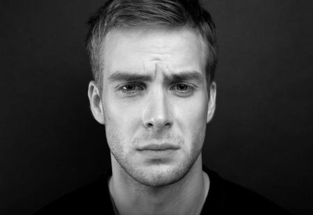 raised eyebrow: Black and white portrait photo of young sad man Stock Photo