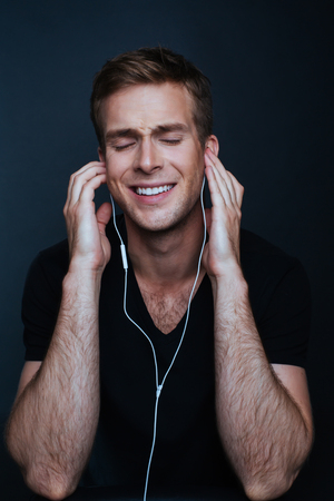 Man is enjoying his favourite music with black shirt on Stock Photo