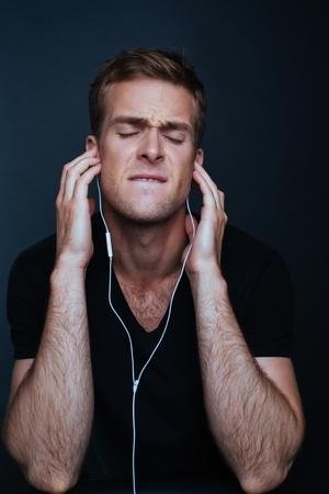Man is listening to music on white earphones Stock Photo