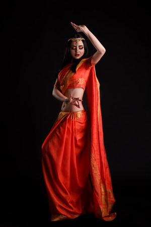 Happy young indian woman in sari dancing on black background. Stockfoto