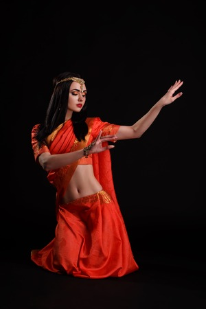 Indian dancer in traditional beautiful red dress dancing in studio. Stock Photo