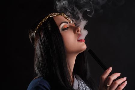 destructive: Beauty portrait of young curly brunette woman enjoying the hookah. Stock Photo