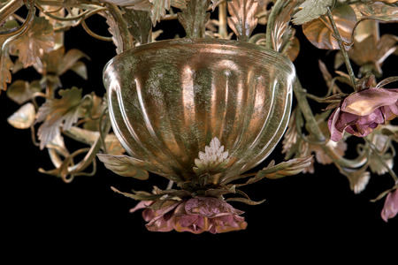 Chandelier close-up classic bronze with curly lampshades flowers and gold leaves.