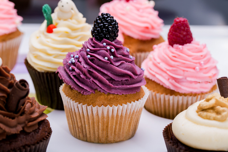 colorful cupcakes with different Tastes. Small beautifull cakes on white table top. Close up Stockfoto