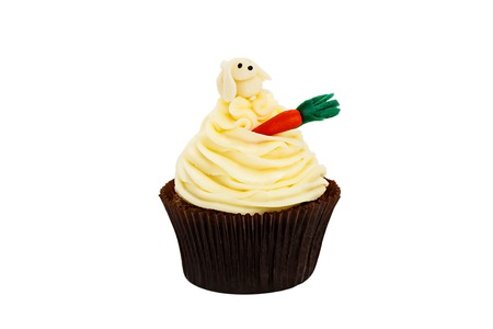 chantilly: creamy sweet cupcake decorated tiny candy carrot on a white background. Stock Photo