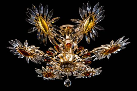 Contemporary gold chandelier isolated on black background. Crystal chandelier decorated amber crystals close-up