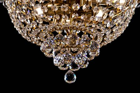 Large crystal chandelier detail isolated on black background. Luxury expensive chandelier for living room, Hall of celebration.