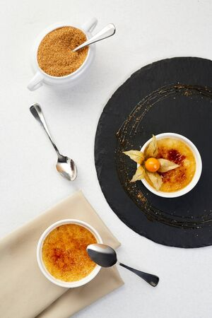 Creme brulee with Physalis and brown sugar. Creme brulee dessert with cofee on black shale.