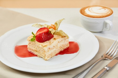 napoleon cake with strawberry, Physalis and jam on white plate. mille-feuille dessert with coffee and cutlery on the table