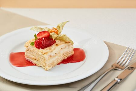 napoleon cake with strawberry, Physalis and jam on white plate. mille-feuille dessert with fresh berries and cutlery.
