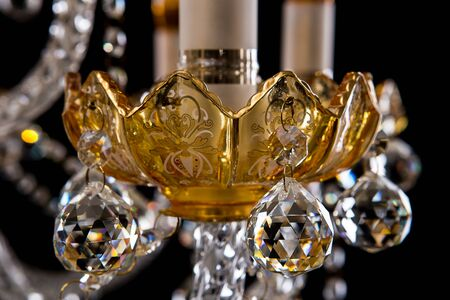 Large crystal close-up chandelier with candles isolated on black background. Luxury royal expensive chandelier for living room, Hall of celebration.