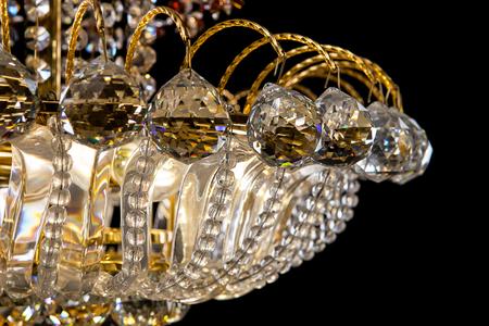 Large crystal chandelier details isolated on black background.