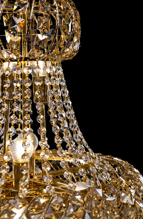 resplandor: Large crystal chandelier close-up in baroque style isolated on black background.