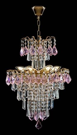 Large crystal chandelier, pink crystals isolated on black background.