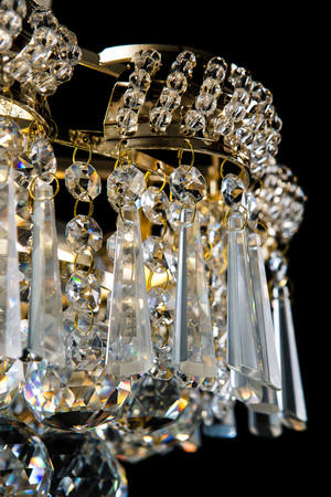 Large crystal chandelier details isolated on black background.