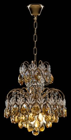 Large crystal chandelier in baroque style isolated on black background.