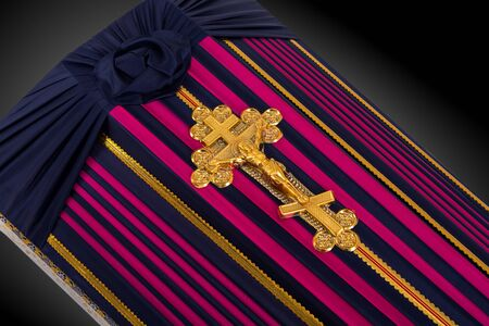 closed coffin covered with color striped cloth decorated with Church gold cross on gray luxury background. Close-up.