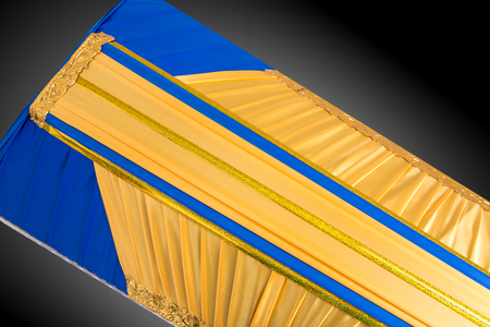 closed yellow and blue coffin covered with elegant cloth isolated on gray background. coffin close-up. Stock Photo