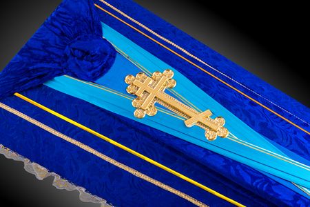 closed blue coffin covered with cloth isolated on gray background. coffin close-up with gold Church cross.