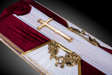closed coffin covered with bordo and white cloth decorated with Church gold cross on gray luxury background. Close-up.