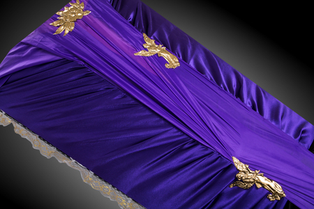 closed purple coffin covered with elegant cloth isolated on gray background. coffin close-up with gold flowers.