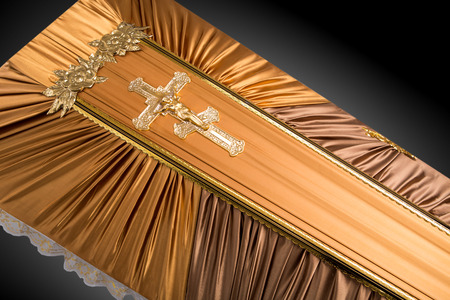 closed beige coffin covered with cloth isolated on gray background. coffin close-up with gold Church cross.