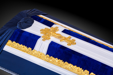 closed coffin covered with blue and white cloth decorated with Church gold cross on gray luxury background. Close-up.