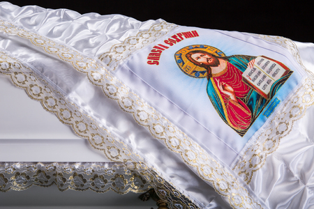 closed wooden white coffin with white silk cloth with a picture of God. close-up on dark royal background.