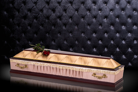 closed wooden beige coffin with red roses covered with cloth isolated on gray luxury background. casket with shadow.