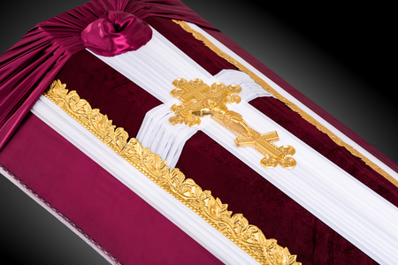 ritual: closed coffin covered with red and white cloth decorated with Church gold cross on gray luxury background. Close-up.